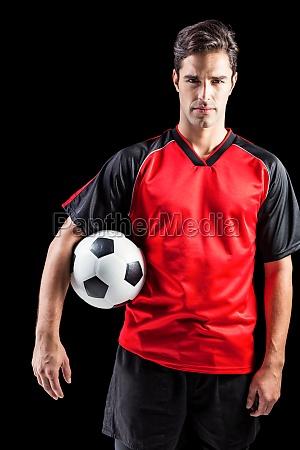 portrait of confident male athlete holding