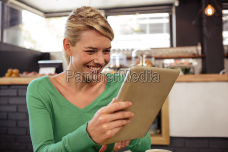 woman using a tablet sitting and
