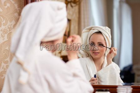 woman applying mascara for eyelashes