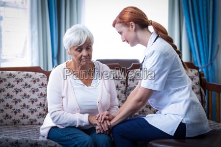 female doctor consoling senior woman in