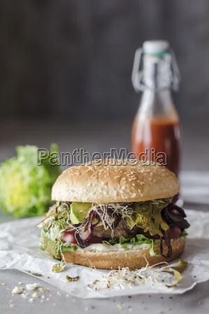 a hamburger with seaweed bacon bean