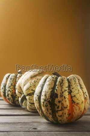 an arrangement of three pumpkins against