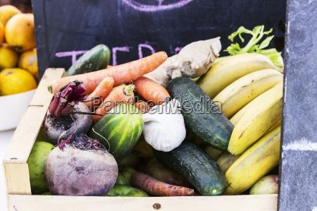 a wooden basket of different vegetables