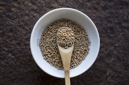 mustard seeds with a wooden spoon