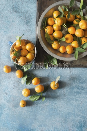 clementines with leaves in a bowl