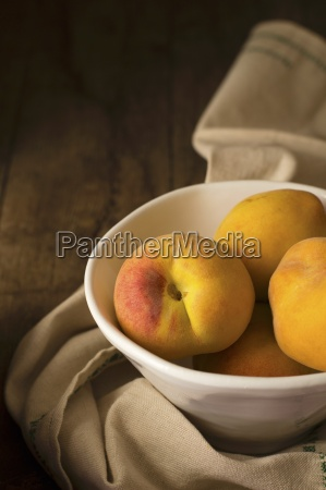 peaches in a ceramic bowl on