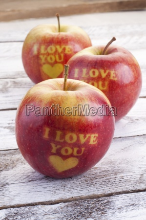 three red apples carved with hearts