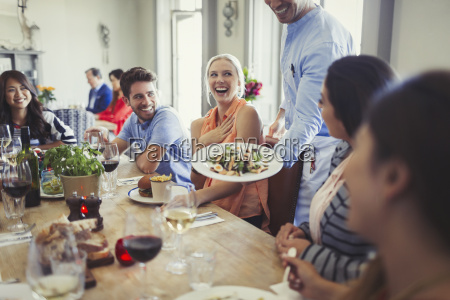waiter serving salad to woman dining