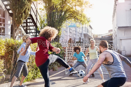 friends playing soccer in sunny summer