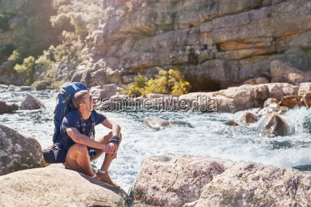 young man with backpack hiking resting