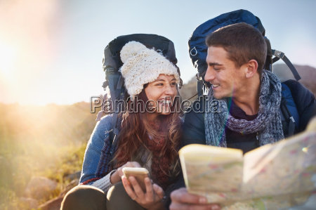 young couple with backpacks hiking checking