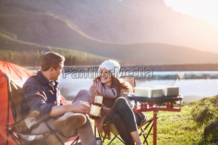 smiling young couple drinking coffee at