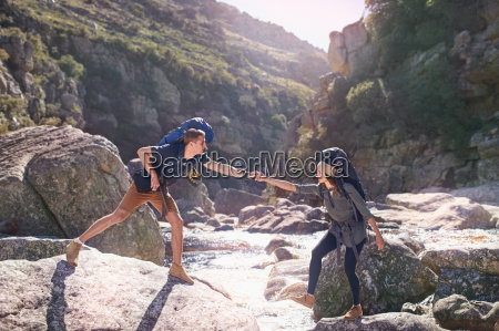 young man helping girlfriend hiking crossing
