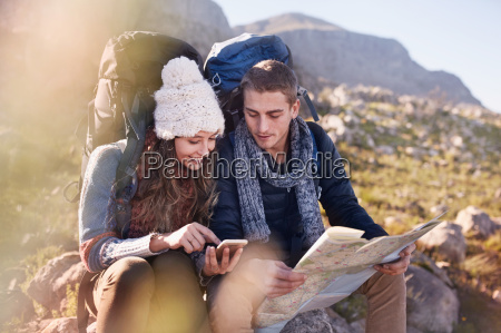 young couple with backpacks hiking resting