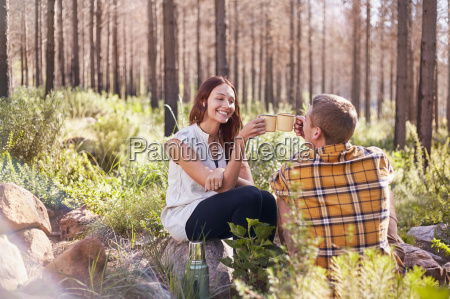 young couple camping toasting coffee mugs