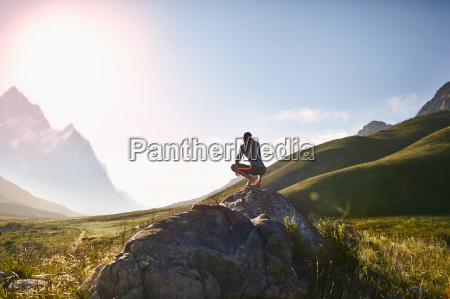 young man crouching on rock looking
