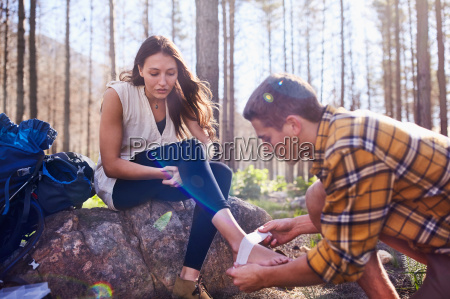young man hiking bandaging girlfriends ankle