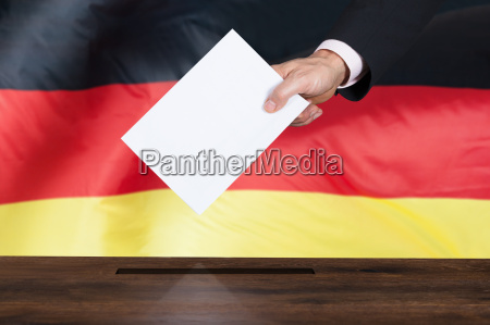 person putting vote in a ballot