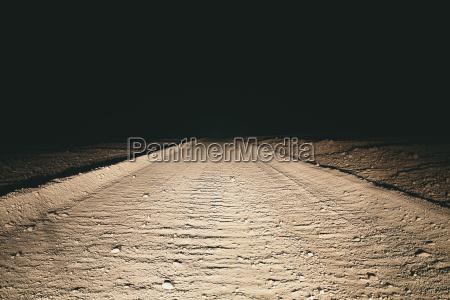 dirt road in desert illuminated by