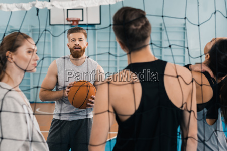 bearded young sportsman with ball talking