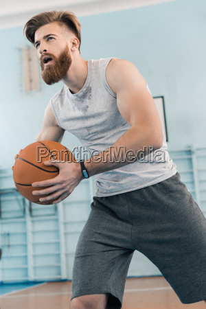 bearded young athletic man playing basketball