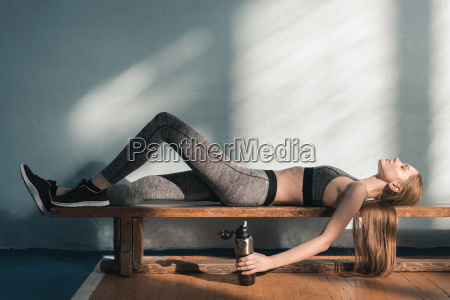 tired sporty woman lying on bench