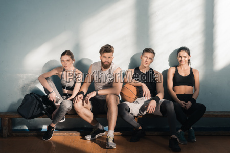 tired sporty men and women sitting