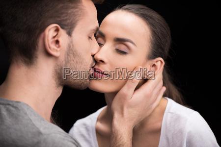 portrait of man sensually kissing woman