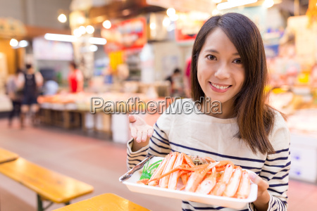 woman, holding, pack, of, snow, crab - 20506841