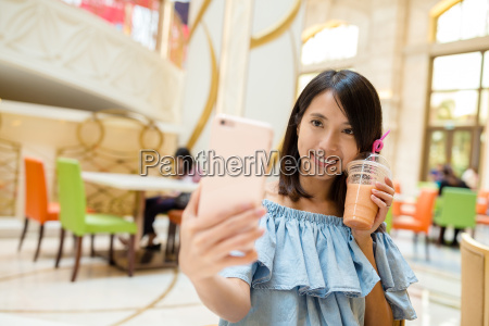 woman, taking, photo, with, her, drink - 20506645