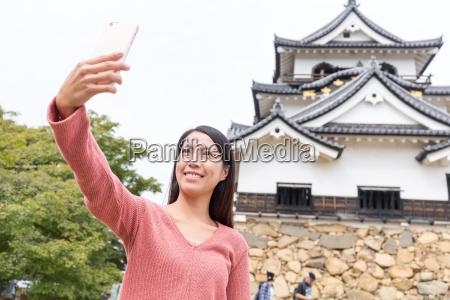 woman, taking, selfie, in, hikone, castle - 20506621