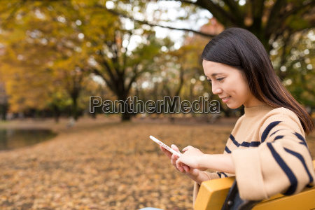 woman, using, cellphone, at, park - 20506899