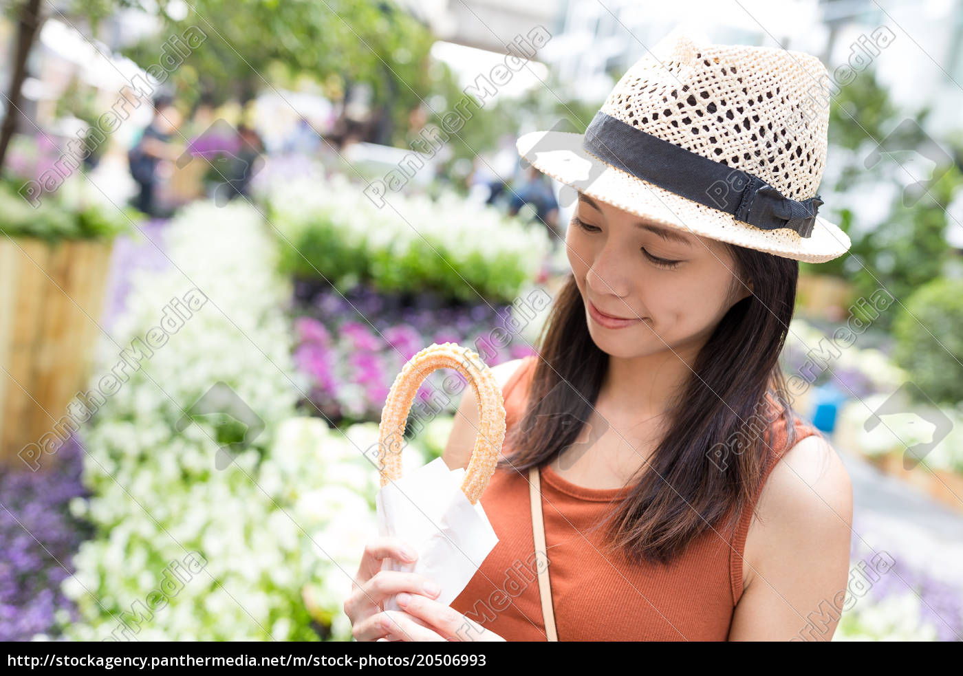 young, woman, holding, spanish, churro, in - 20506993