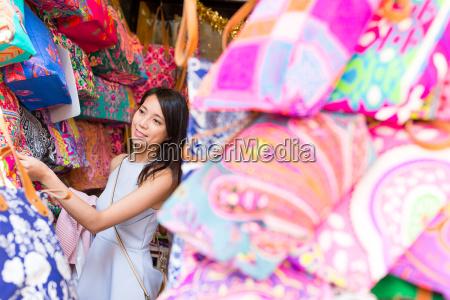 woman buying bag in street market