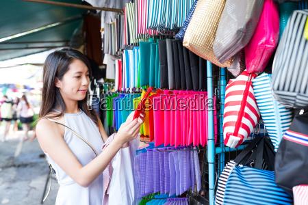 woman, buying, bag, at, street, market - 20507003