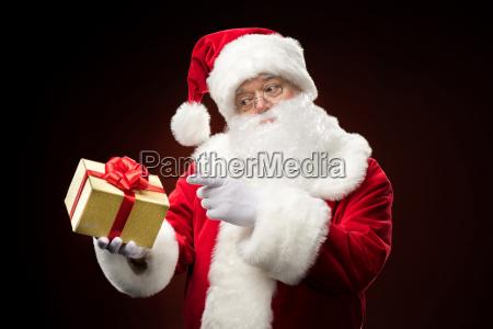 santa claus pointing on gift box
