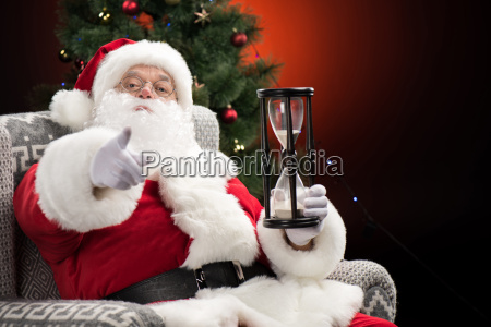 santa claus with hourglass pointing