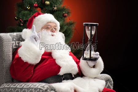 santa claus sitting with hourglass