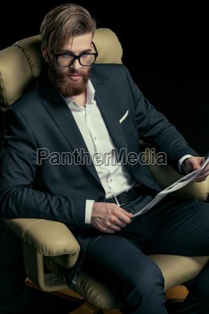 stylish businessman in eyeglasses holding newspaper