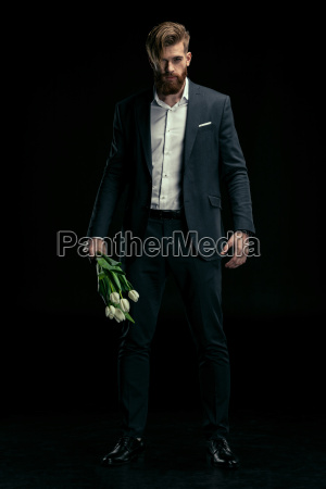stylish man in suit holding tulips