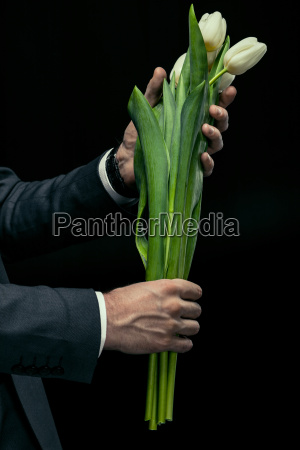 partial view of man holding tulips