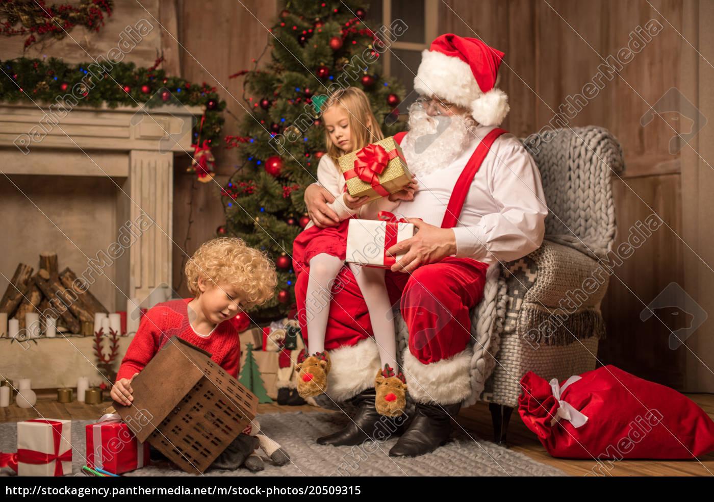 santa, claus, with, children, sitting, near - 20509315