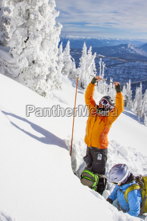 two female skiers dig a snow