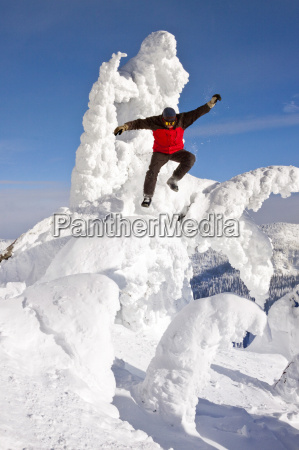 male snowboarder jumping off a snow