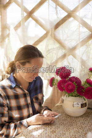 young woman with mobilephone and flowers