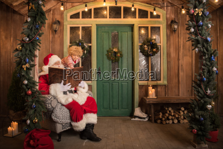 santa claus with child reading book