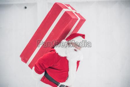 santa claus carrying gift box
