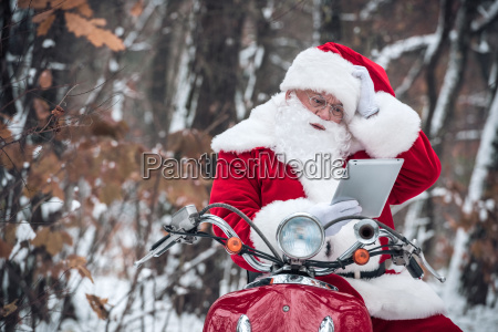 santa claus on scooter using tablet