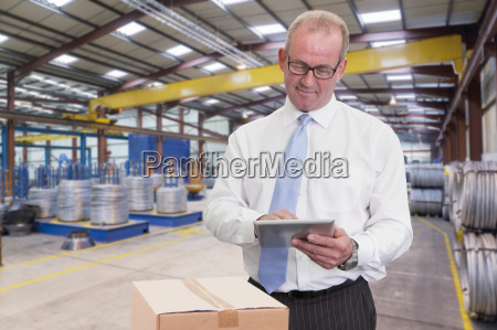 businessman in warehouse dispatch area with