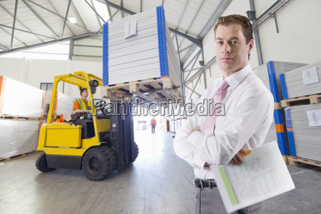 businessman in solar panel manufacturing warehouse